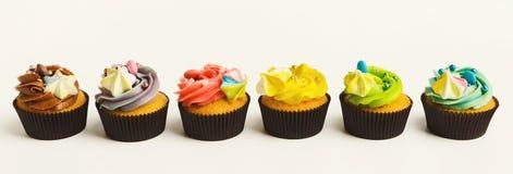 Smakelijke die muffins met buttercream op wit wordt geïsoleerd royalty-vrije stock afbeelding