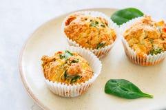 Smakelijke die van aardappelspinazie en feta muffins op een plaat worden gediend wit Stock Afbeeldingen