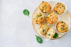 Smakelijke die van aardappelspinazie en feta muffins op een plaat worden gediend wit Stock Afbeelding