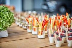 Smakelijke die voorgerechten in glaskruiken worden gediend op houten lijst stock foto