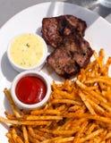 Smakelijke dinerplaat met aardappels, lapje vlees en kruiden Royalty-vrije Stock Foto's