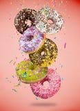 Smakelijke doughnuts in motie die op pastelkleur blauwe achtergrond vallen royalty-vrije stock afbeelding