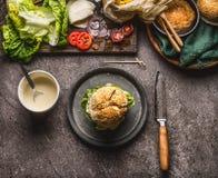 Smakelijke eigengemaakte hamburger op plaat met mes en ingrediënten op donkere rustieke achtergrond royalty-vrije stock afbeelding