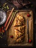 Smakelijke eigengemaakte rabarber en van de aardbeienstrudel gebakjepastei op donkere rustieke keukenlijst, hoogste mening Seizoe royalty-vrije stock fotografie