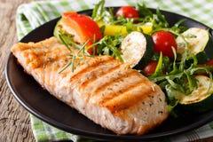 Smakelijke filet van geroosterde zalm en plantaardige salade met arugula stock fotografie