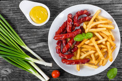 Smakelijke frieten en worsten op plaat, hoogste mening stock foto's