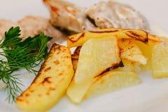 Smakelijke gebraden aardappels met greens en varkensvleesvlees Stock Foto's