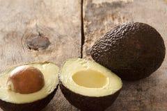 Smakelijke gehele en gehalveerde rijpe avocado's stock afbeelding