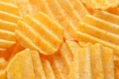 Smakelijke gepelde spaanders met paprika De achtergrond van voedselspaanders foo stock afbeelding