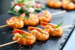 Smakelijke geroosterde garnalen op vleespen Stock Afbeelding