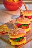 Smakelijke geroosterde rundvleesburgers met sla, tomaat, kaas en mayonaise op rustieke houten raad Naar huis gemaakte gamburgers  royalty-vrije stock afbeelding