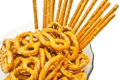 Smakelijke gezouten pretzels en breadsticks op een plaat Royalty-vrije Stock Foto