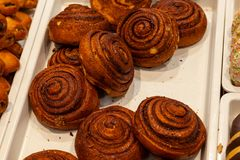 Smakelijke grote bruine broodjes met kaneel in de vorm van spiralen c stock fotografie