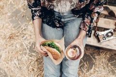 Smakelijke hamburger en limonade in handen, hoogste mening modieuze hipster wo royalty-vrije stock afbeelding