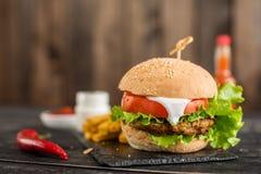 Smakelijke hamburger met vlees en groenten tegen een donkere achtergrond Royalty-vrije Stock Afbeeldingen