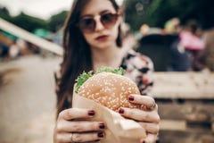 Smakelijke hamburger modieuze hipstervrouw die sappige hamburger in h houden royalty-vrije stock afbeelding