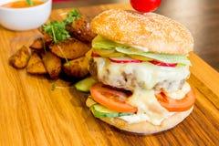 Smakelijke hamburger op een houten schotel stock afbeeldingen