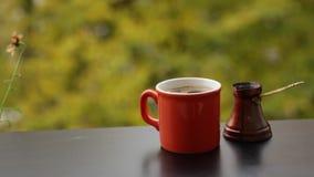 Smakelijke hete donkere die koffie in traditionele Turkse koffiepot wordt gebrouwen, koffielijst op veranda stock video