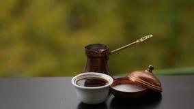 Smakelijke hete koffie in witte die koffiekop met suiker in traditionele Turkse pot, koffielijst in openlucht wordt gebrouwen stock video