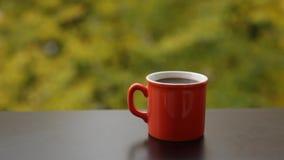 Smakelijke hete stomende koffie in rode kop, koffielijst op veranda stock video