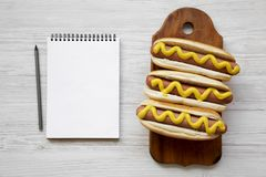 Smakelijke hotdog met gele mosterd op houten raad en lege blocnote op witte houten achtergrond, hoogste mening Vlak leg, overhead Royalty-vrije Stock Afbeeldingen
