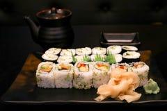 Smakelijke Japanse sushi op een zwarte plaat met schotel op de zwarte lijst Stock Afbeelding