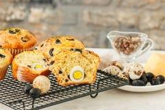 Smakelijke muffins met olijven, kwartelseieren en kruiden op een draadrek stock foto