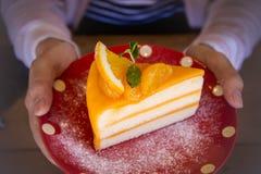 Smakelijke oranje fruitcake op rode Kerstmis patt schotel voor klaar aan royalty-vrije stock foto