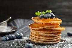 Smakelijke pannekoeken met bessen en honing stock foto's