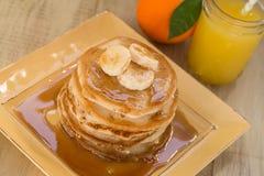 Smakelijke Pannekoeken met Stroop en Bananen en Vers Jus d'orange stock afbeelding