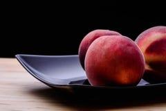 Smakelijke perziken op donkere plaat Stock Foto's