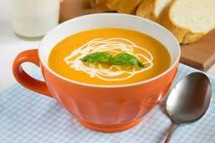 Smakelijke pompoensoep met room in oranje kom Royalty-vrije Stock Foto's