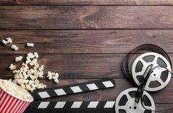 Smakelijke popcorn, filmspoel en dakspaan stock afbeelding
