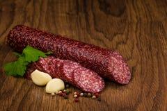 Smakelijke salamiworst op houten achtergrond Stock Afbeelding