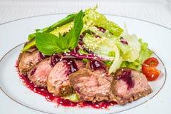 Smakelijke, smakelijke stukken van gehakt vlees met saus, tomaten en kruiden, op een witte plaat Horizontaal kader stock foto