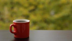 Smakelijke stomende hete koffie in rode kop, koffielijst in openlucht stock videobeelden