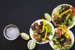 Smakelijke taco's met rundvlees en groenten, bier en kalk op een zwarte achtergrond, hoogste mening Mexicaanse keuken Stock Afbeeldingen