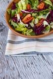 Smakelijke tomatensalade in kom op houten lijst Selectieve nadruk Stock Fotografie