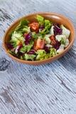 Smakelijke tomatensalade in kom op houten lijst Selectieve nadruk Stock Foto