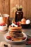Smakelijke traditionele Amerikaanse pannekoeken in stapel met zure room, verse aardbeien en bosbessen op witte plaat dichtbij kom royalty-vrije stock foto's