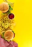 Smakelijke verse ongezonde hamburgers met ketchup en groenten en stock afbeelding