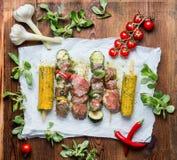 Smakelijke Vleesvleespennen voor grill met groenten, korenaren en specerij op rustieke achtergrond Royalty-vrije Stock Afbeelding