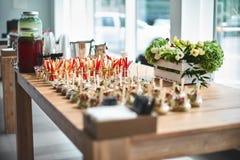 Smakelijke voorgerechten met houten die lepels in glaskruiken worden gediend op houten lijst stock foto's