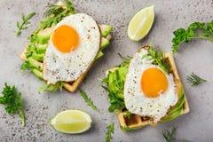Smakelijke wafels met avocado, arugula en gebraden ei voor ontbijt royalty-vrije stock afbeelding
