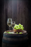 Smakelijke witte wijn in glas met druiven op oud vat Stock Fotografie