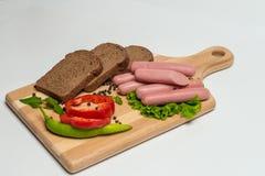 Smakelijke worst en brood met sla en tomaat voor lunch en diner royalty-vrije stock foto's