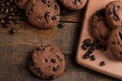 Smakelijke zoete koekjes met chocolade en korrels van koffie op een bruine houten lijst Mening van hierboven royalty-vrije stock afbeeldingen