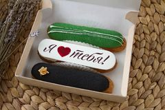 Smakelijke zoete ontwerper drie eclairs met verschillende vullingen en de inschrijvings` I liefde u ` in een kartonvakje op de li Stock Foto's