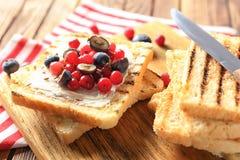 Smakelijke zoete toosts met boter en verse bessen op houten raad, close-up royalty-vrije stock foto