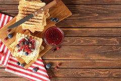 Smakelijke zoete toosts met jam en verse bessen op houten lijst stock fotografie